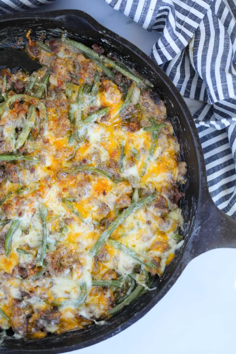 ground beef green bean casserole vertical image in a skillet with melted cheese on top sitting on a white background