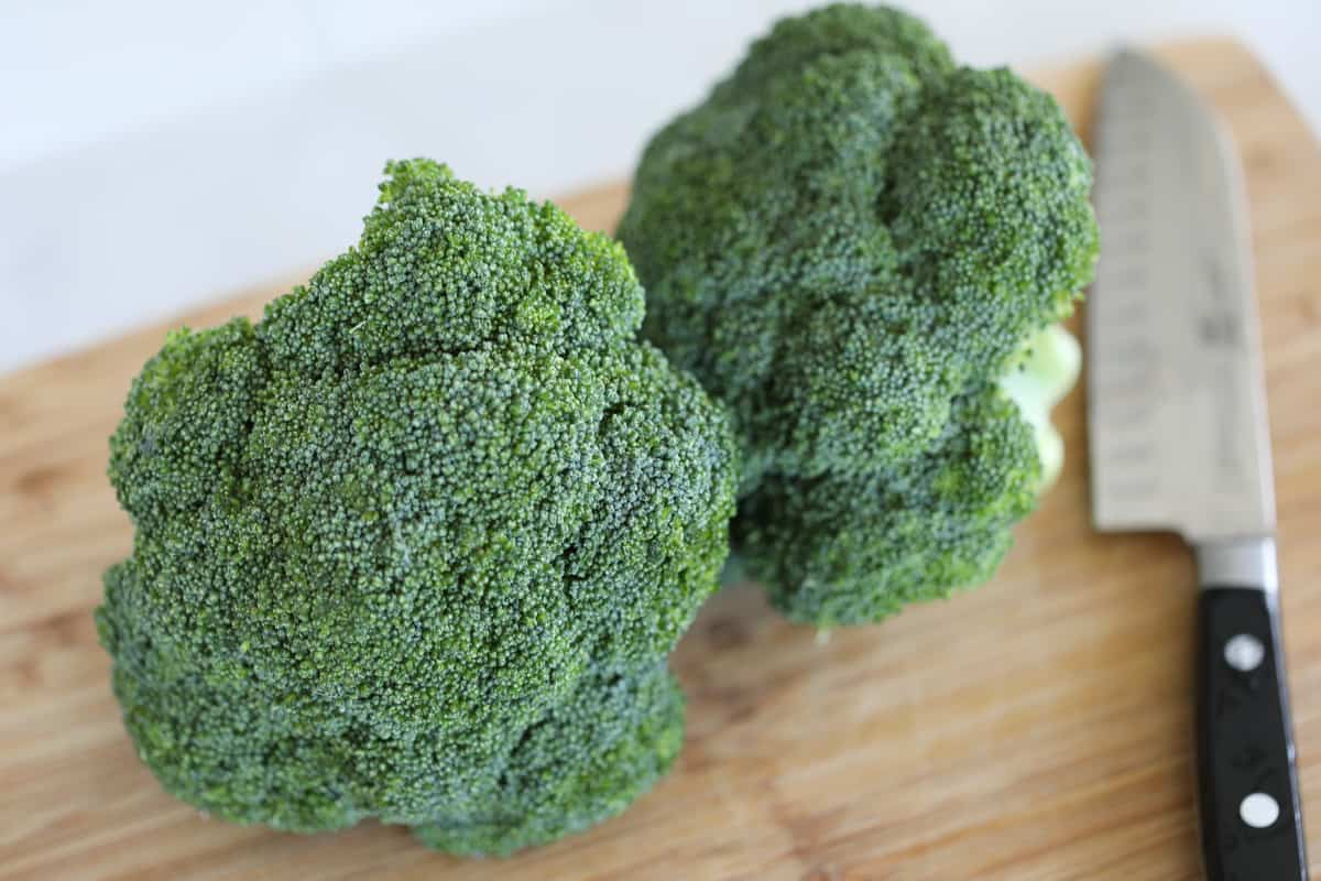 how to steam broccoli in the microwave starts with prepping and cutting the raw broccoli florets into bite sized pieces