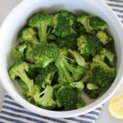 how to steam broccoli in the microwave, photo after cooking with lemon served on the side in a white dish