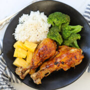 instant pot chicken drumsticks on a black plate with broccoli and rice