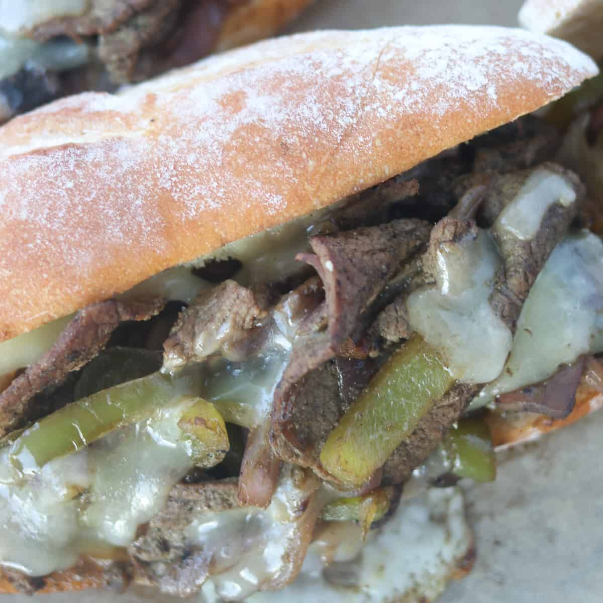 the best philly cheesesteak recipe closeup image with hot melted cheese