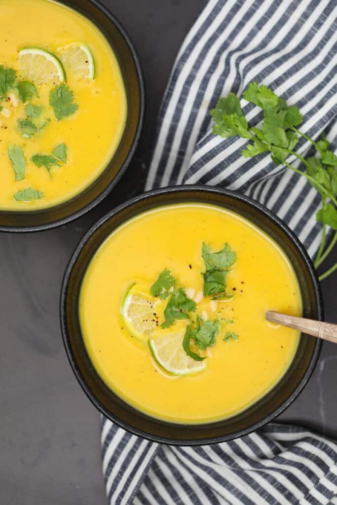 butternut squash soup paleo recipe in a black bowl on a black background