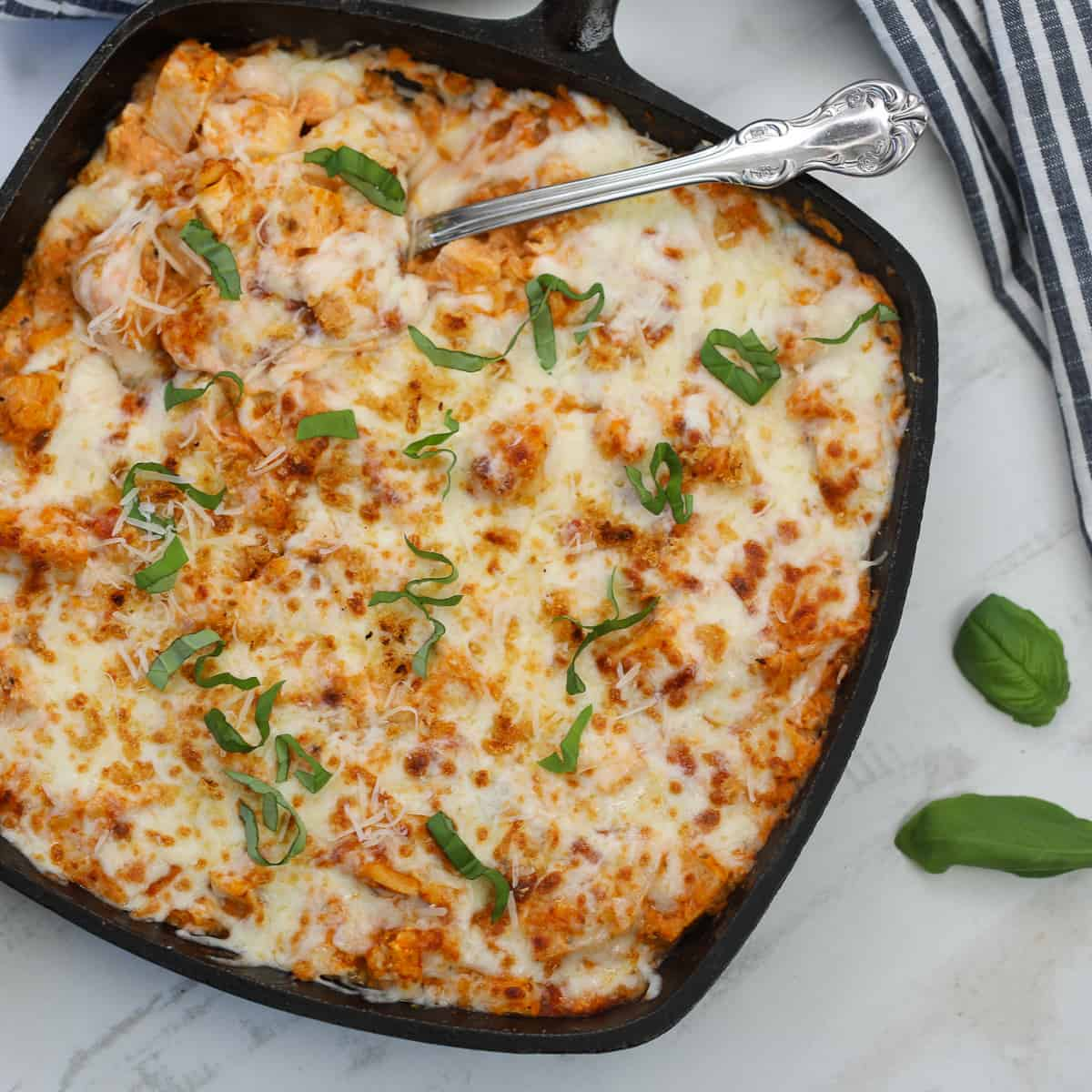 chicken parm casserole in a skillet with basil