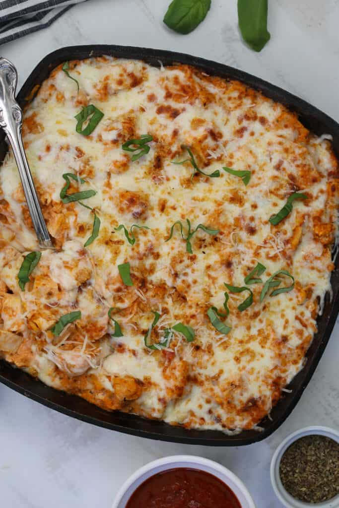 keto chicken parmesan casserole in a skillet on a gray background