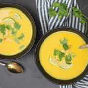 paleo butternut squash soup in a bowl with cilantro and limes
