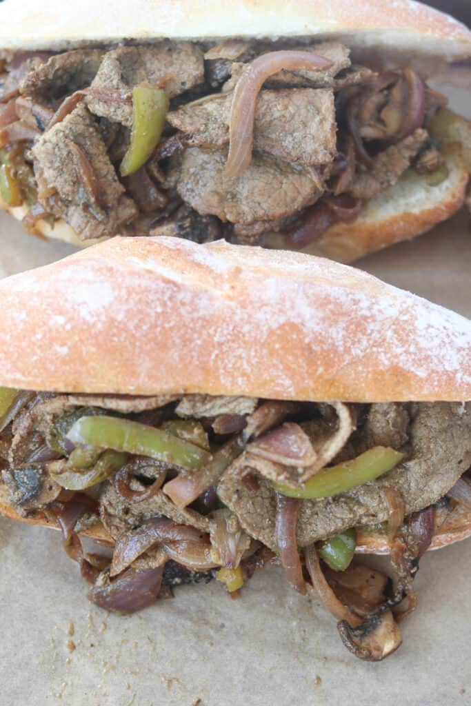 the Philly steak and cheese recipe getting stuffed into hoagie rolls