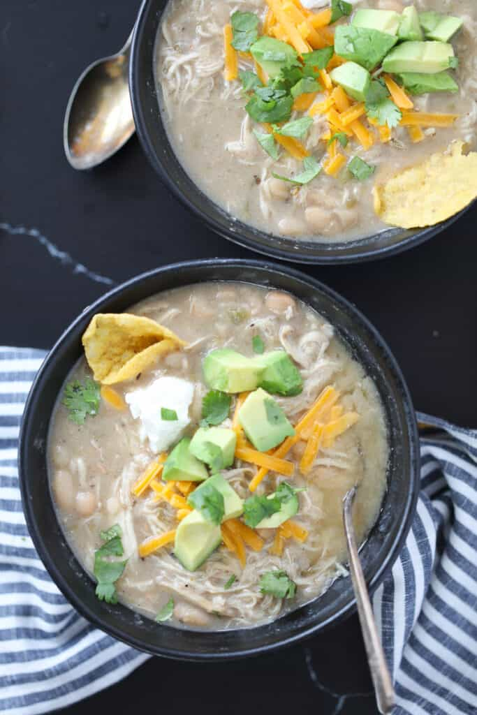 white bean chicken chili instant pot recipe in black bowls with cheese