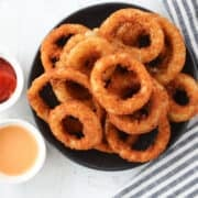 air fryer frozen onion rings on a black plate after cooking