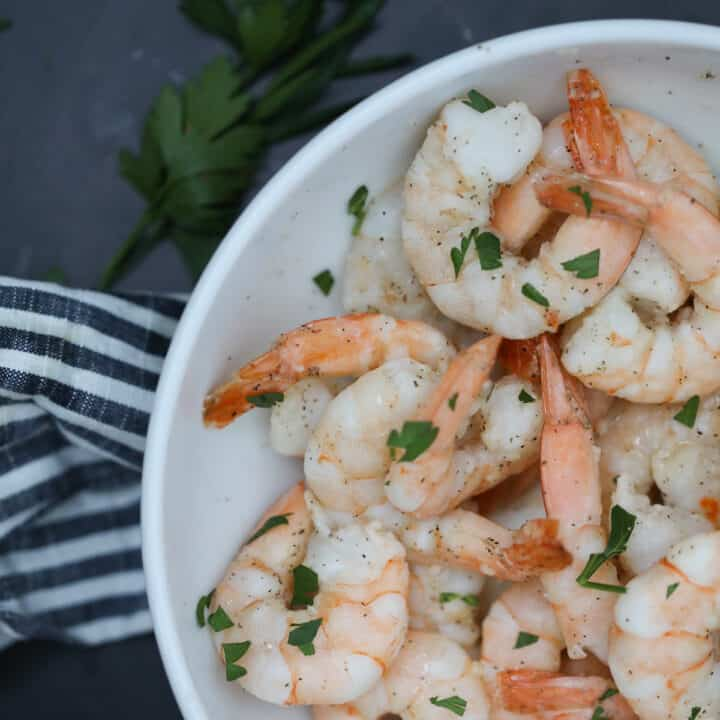 air fryer frozen shrimp with garlic butter in a white bowl on a black background