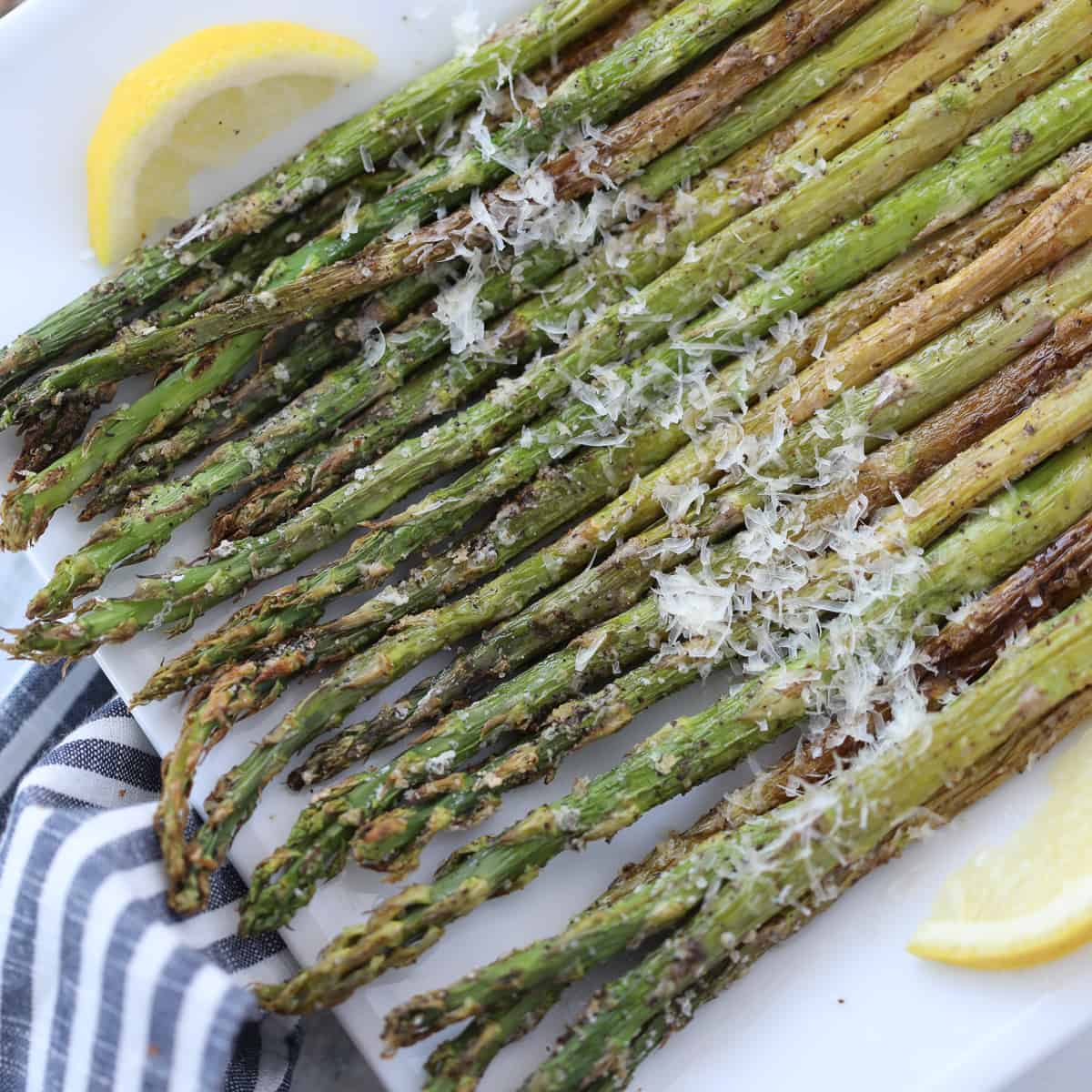 asparagus in air fryer topped with parmesan on a white plate