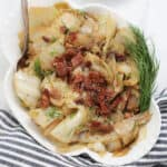 crock pot cabbage in a white bowl garnished with dill and bacon