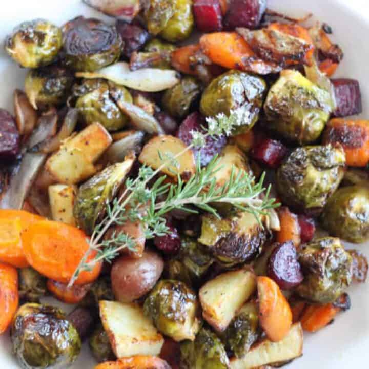 fall roasted vegetable in a white bowl topped with rosemary