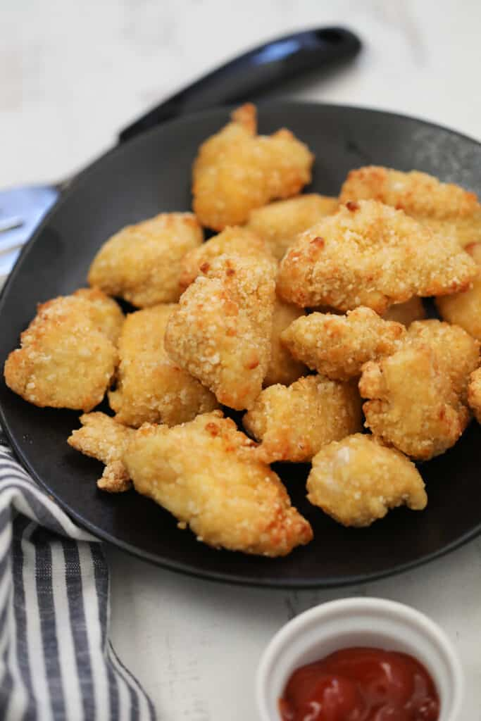 frozen chicken nuggets in air fryer recipe on a black plate with sauce