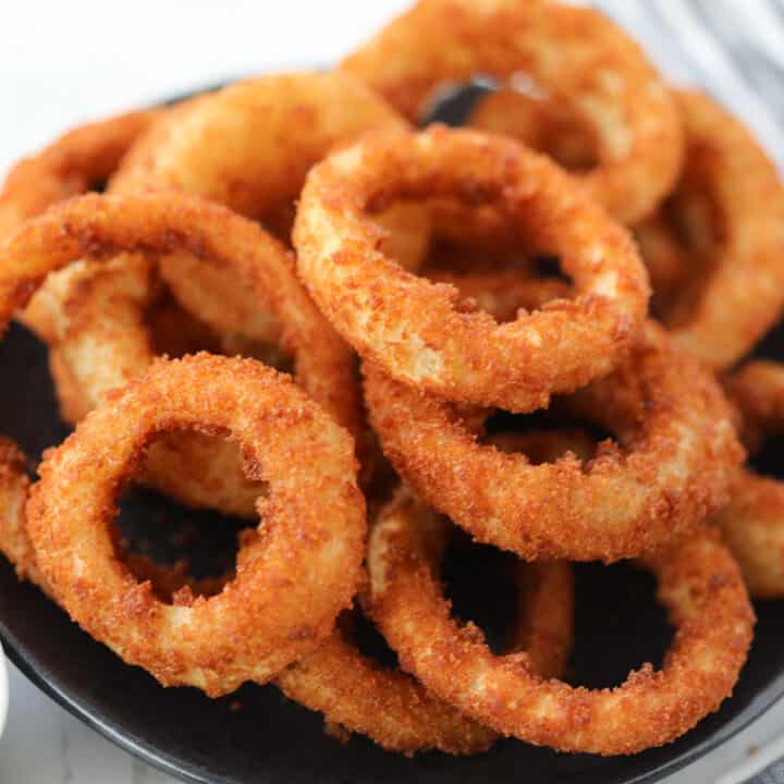 frozen onion rings air fryer recipe stacked up on a plate