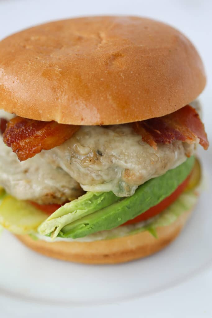 the turkey burgers in air fryer recipe on a bun with bacon and toppings