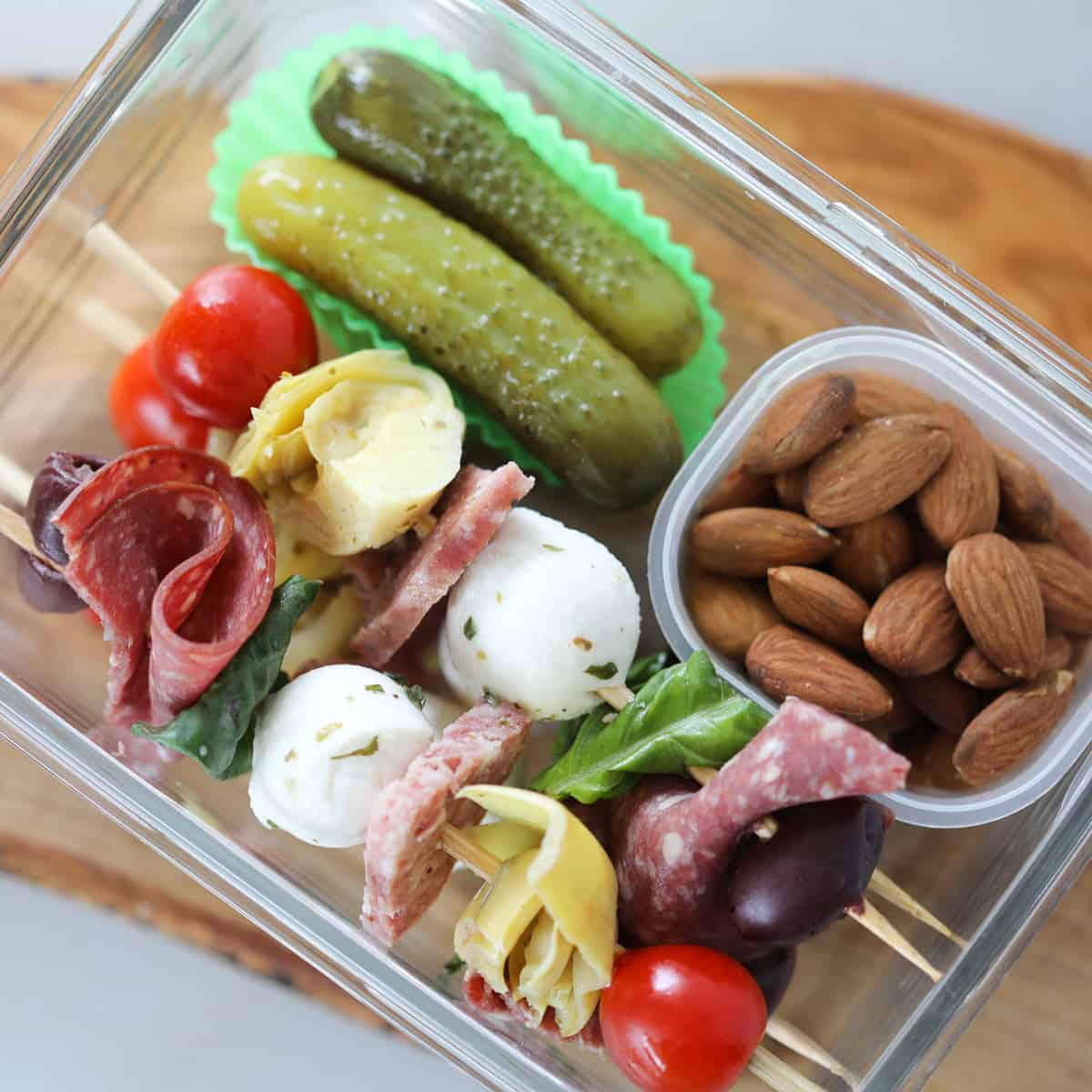 the antipasto skewers keto recipe makes a great low carb lunch, shown in a meal prep conntainer with nuts and pickles