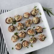 bacon cream cheese stuffed mushrooms on a white plate