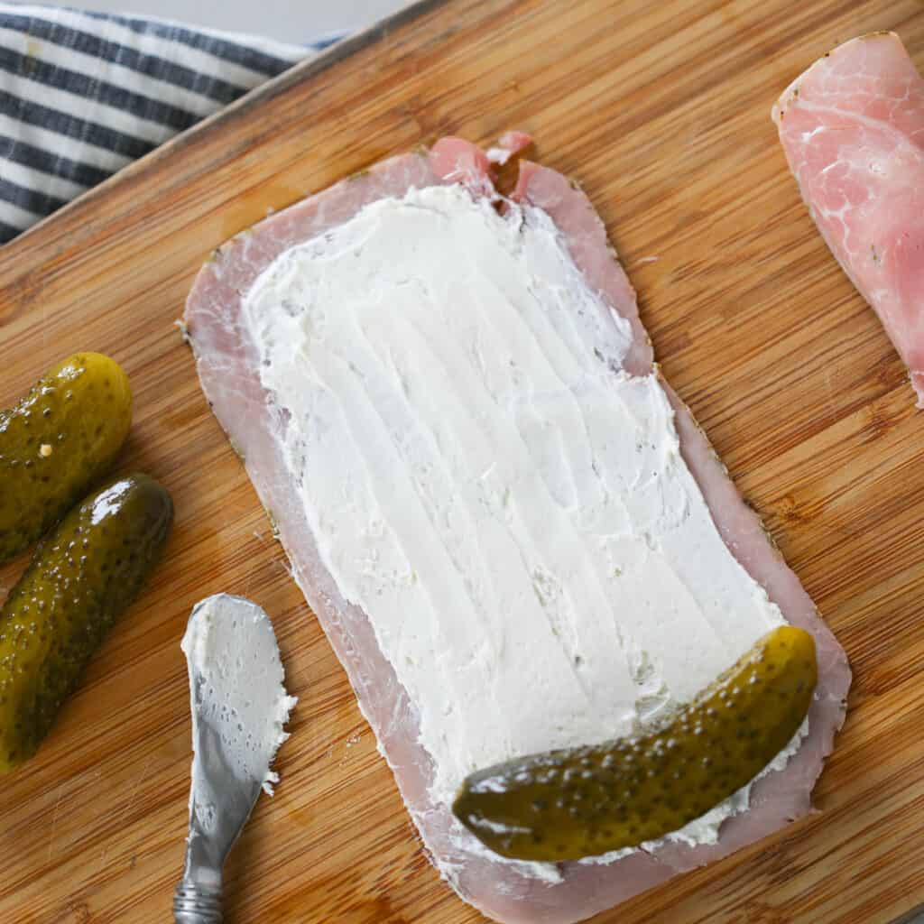 rolling the pickle cream cheese ham snack into logs