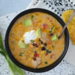 instant pot chicken taco soup with sour cream and cheddar cheese on a white background
