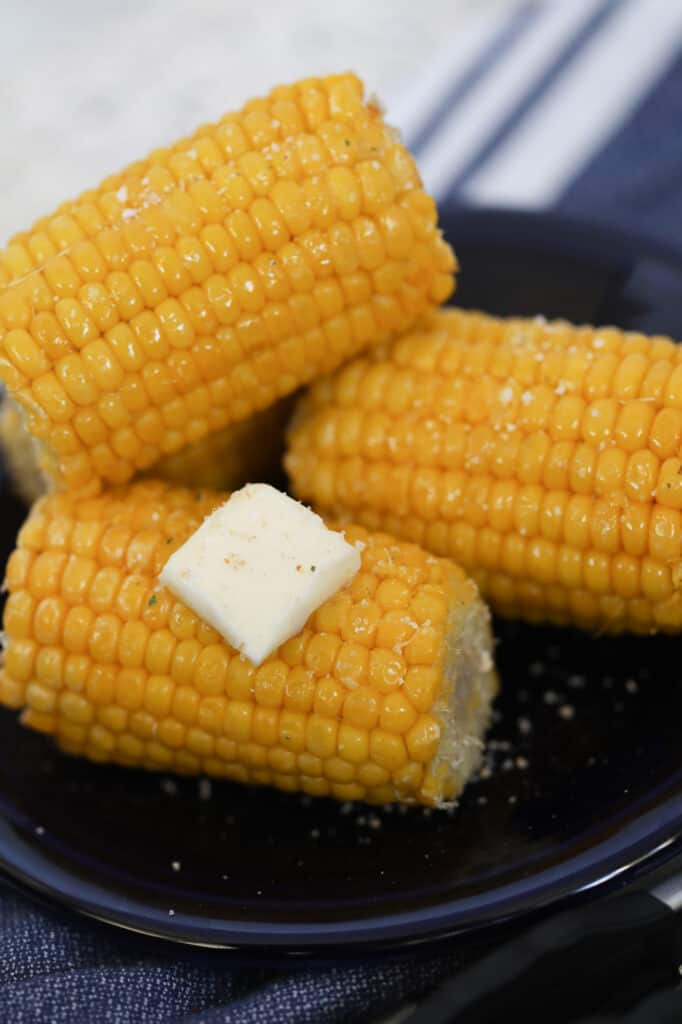 air fryer frozen corn on the cob on a blue plate with butter