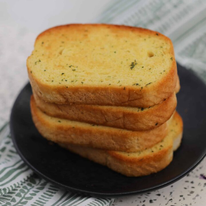 air fryer frozen garlic bread stacked on a black plate
