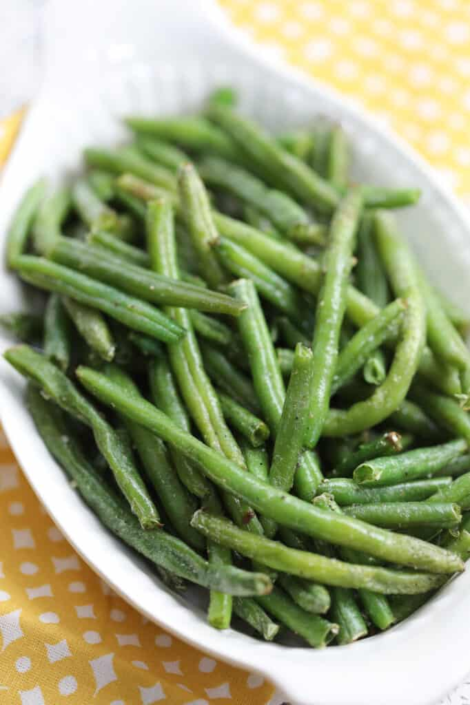 air fryer frozen green beans in a white serving dish with a yellow cloth
