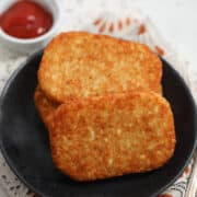 air fryer frozen hash browns on a black plate with ketchup