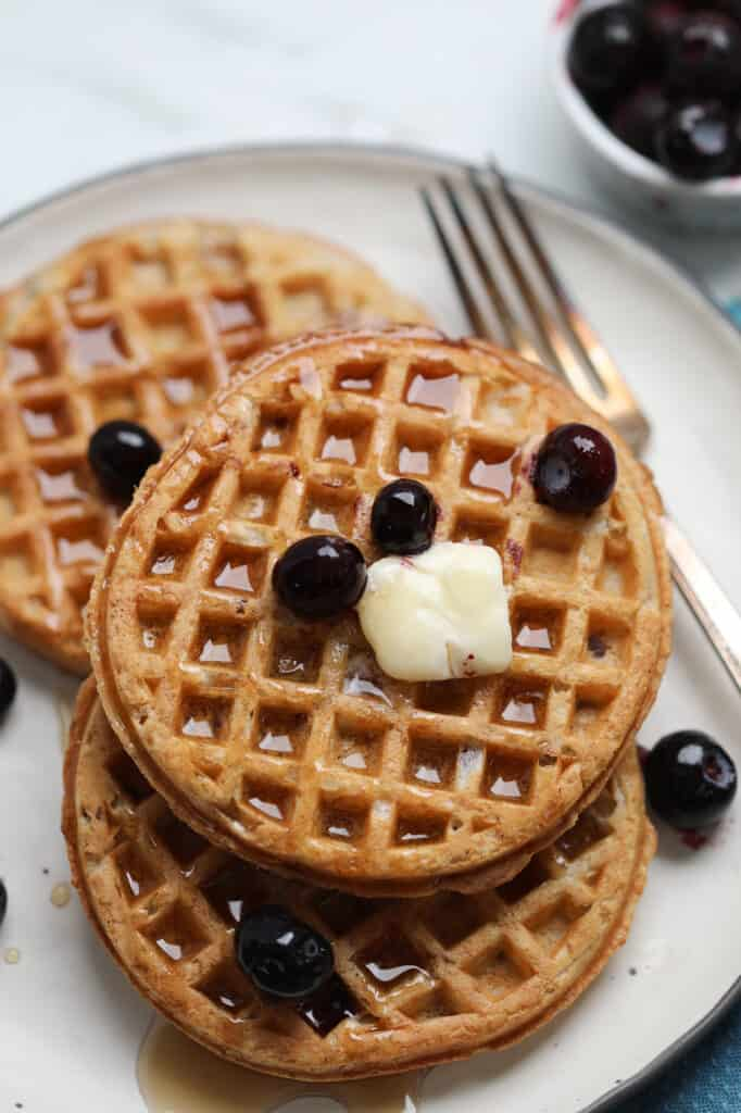 air fryer frozen waffles on a white plate with butter and blueberries