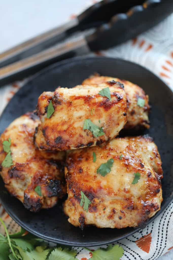 the frozen chicken thighs in air fryer recipe with cilantro on a black plate