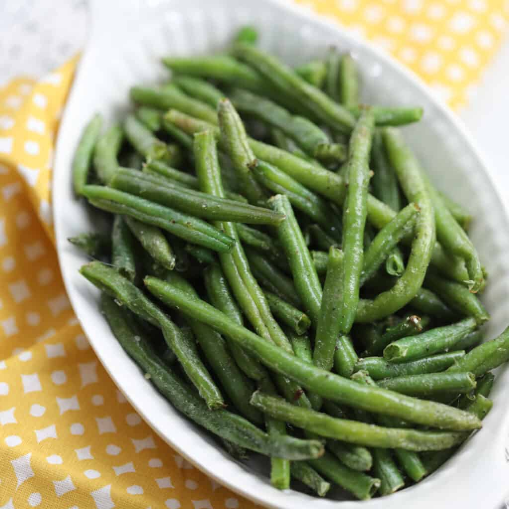 frozen green beans in air fryer ready to serve in a white dish that are healthy