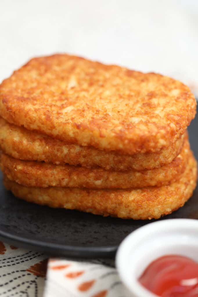 frozen hash browns in air fryer stacked on a black plate