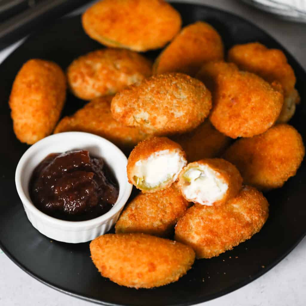 frozen jalapeno poppers in air fryer after cooking on a black plate