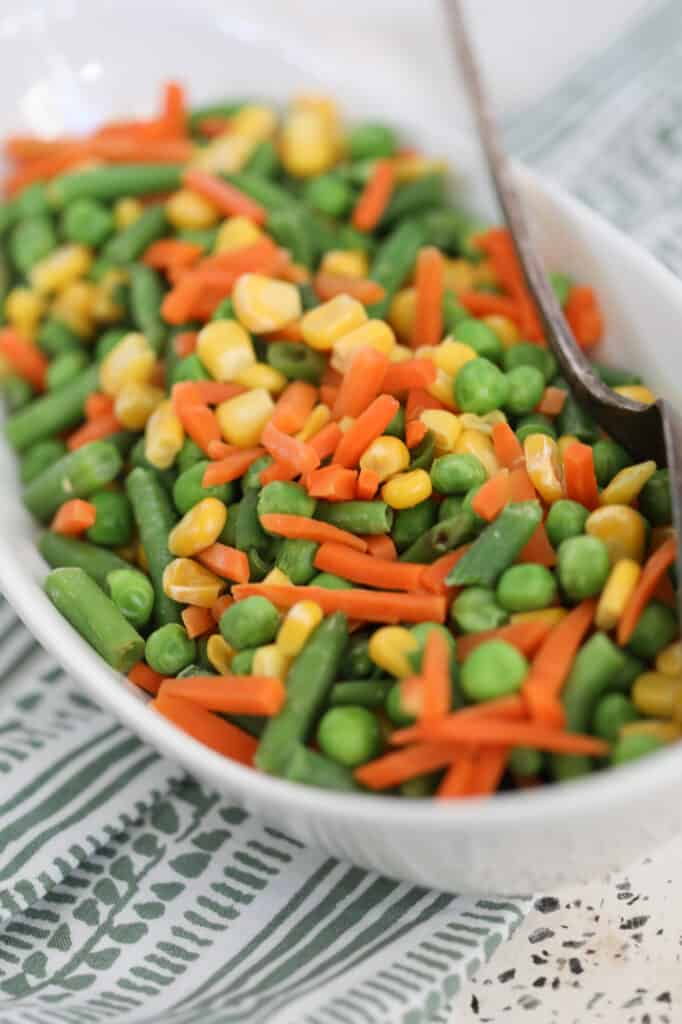 the frozen vegetables in air fryer after cooking in a white serving dish