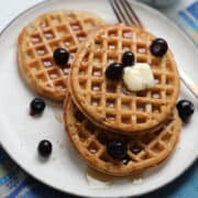 the frozen waffles in air fryer on a white plate with blueberries butter and syrup