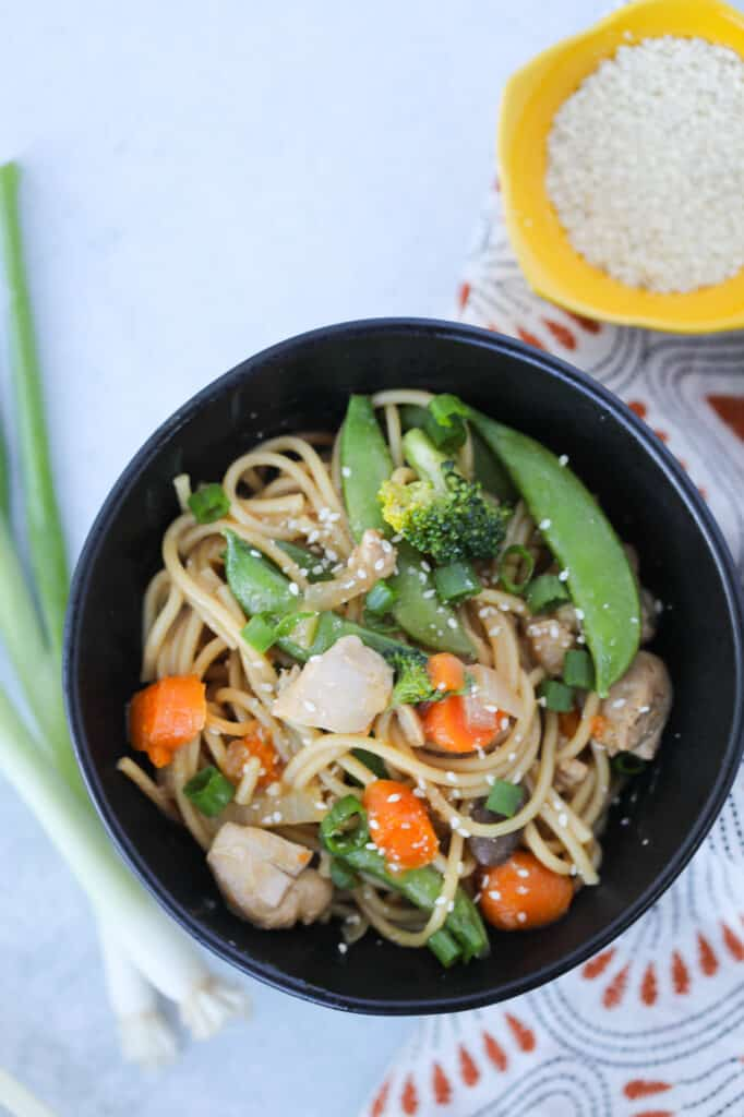 instant pot chicken lo mein in a black bowl with garnishes