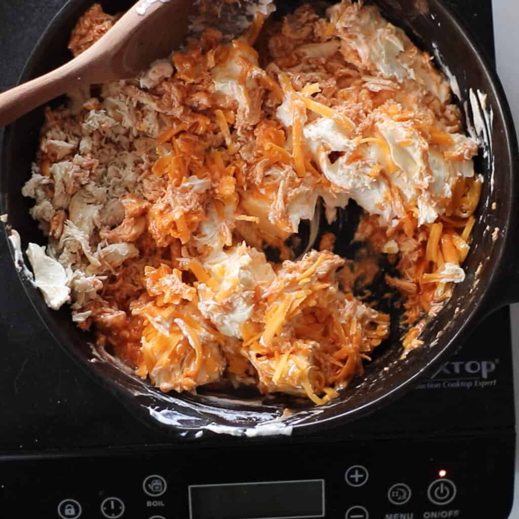 keto buffalo chicken dip ingredients getting added to a pan