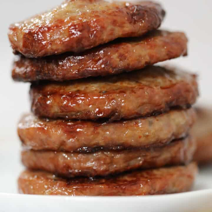 sausage patties in air fryer stacked on a white plate