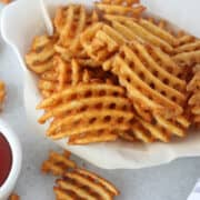 alexia air fryer frozen waffle fries in a white basket ready to eat