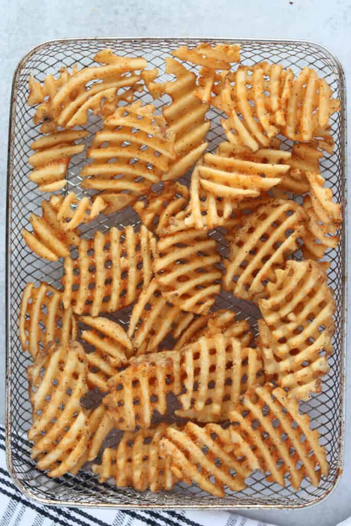 the frozen air fryer waffle fries laying in a basket before cooking
