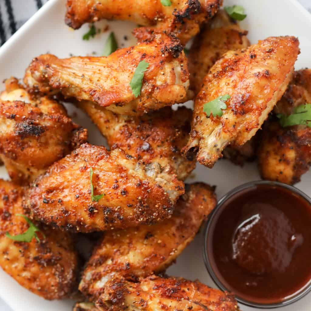 a bbq dry rub for air fryer wings gets sprinkled on the wings and then cooked. serve with bbq sauce