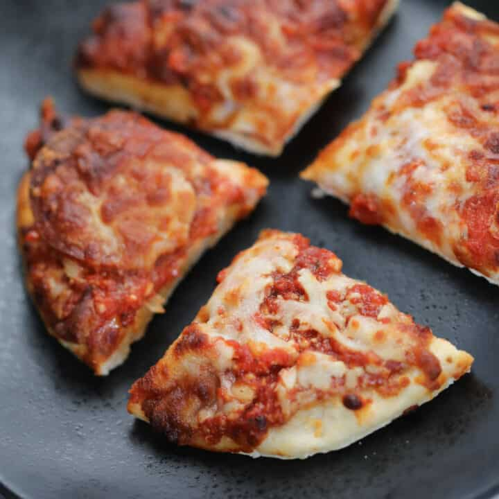 frozen pizza in air fryer cut into 4 on a black plate