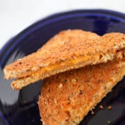 air fryer grilled cheese sandwich cut in half on a blue plate