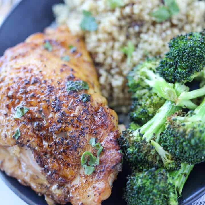 cooked chicken thighs in a pan served with broccoli and rice