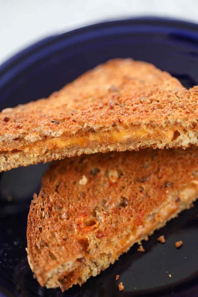 the grilled cheese in air fryer recipe on a blue plate after cooking