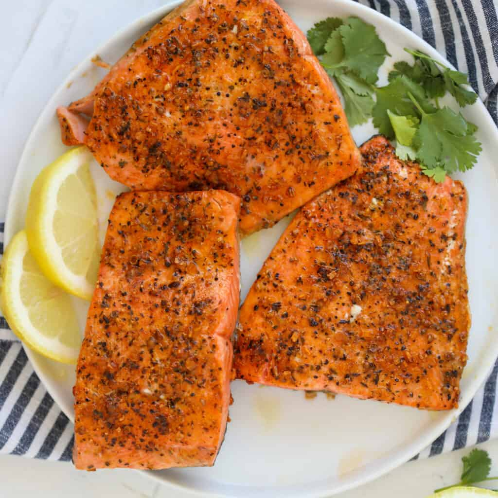 air fryer frozen salmon on a white plate with lemon