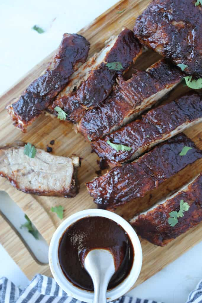 air fryer pork ribs on a cutting board with bbq sauce after cooking
