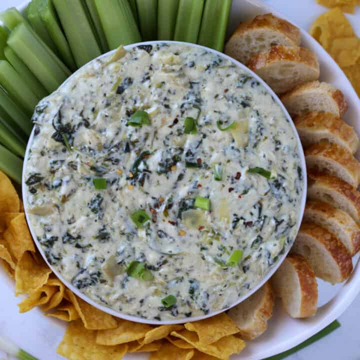instant pot spinach artichoke dip in a white bowl served with bread and chips