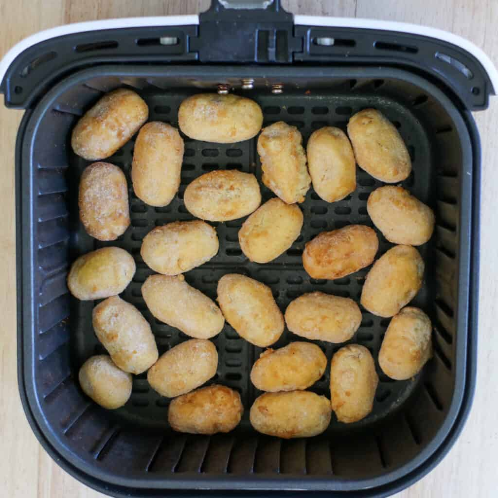 mini corn dogs in air fryer basket before cooking