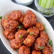 air fryer boneless chicken wings chicken bites from frozen with buffalo hot sauce in a white dish