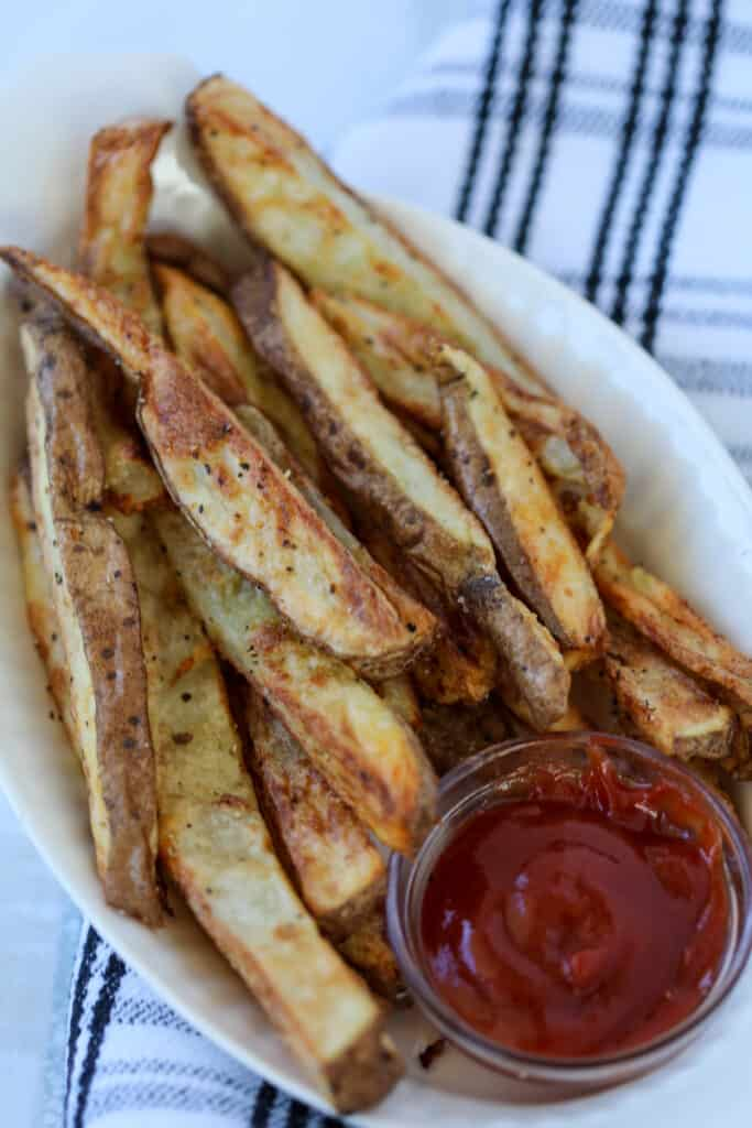 air fryer steak fries after cooking in a white dish